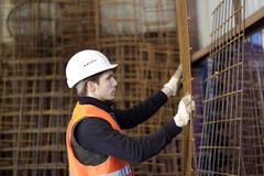 Factory worker moving wire mesh in concrete reinforcement factory - stock photo