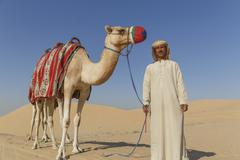 Portrait of bedouin with camel in desert, Dubai, United Arab Emirates Stock Photos