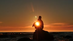 Man silhouette on a rock in the sea thinking dolly shot at sunset Stock Footage