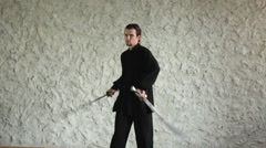 Man practicing elements of tai chi. The man rotating steel swords around a body Stock Footage