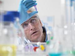 Close up of scientist holding a phial containing a DNA sample - stock photo