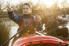 Young woman in canoe looking away, pointing Stock Photos