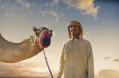 Portrait of camel and bedouin in desert, Dubai, United Arab Emirates Stock Photos
