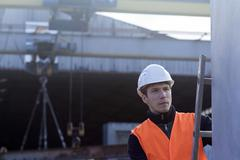 Factory worker on ladder checking concrete block in concrete reinforcement - stock photo