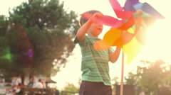 Happy child play with colorful pinwheel at sunset park outdoor Stock Footage