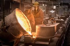 Two workers pouring molten metal from flask in foundry Stock Photos