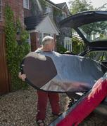 Senior man loading surfboard into car boot - stock photo