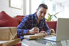 Mid adult man writing address on parcels in picture framers showroom - stock photo