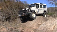 Driving a 4x4 over a large rock in south africa Stock Footage