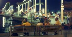 Tourists walks on bridge over Port Vell marina at night. Illuminated bridge Stock Footage