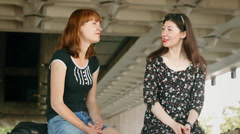 Two beautiful girls talk about their lives sitting on the parapet Stock Footage