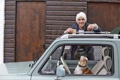Portrait of mid adult man leaning against van whilst dog looks up - stock photo