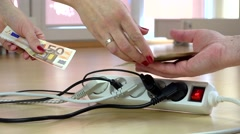 Woman hands pay euro banknotes for electricity usage in front of switch plugs Stock Footage