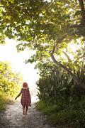 Rear view of barefoot girl in sunhat walking along woodland beach path, Anna - stock photo