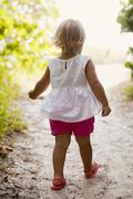 Rear view of female toddler toddling on woodland beach path, Anna Maria Island, - stock photo