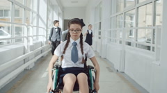 Disabled girl riding wheelchair at school while her friends. Stock Footage
