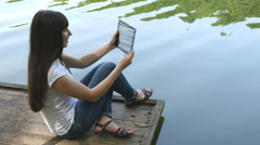Young happy girl sitting on a jetty by a lake and chatting on tablet computer - stock footage