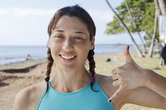 Woman making hand gesture on beach Stock Photos