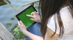 Female hands using tablet pc with green screen sitting on a jetty by the lake. Stock Footage