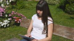 Girl typing on digital tablet computer and sitting on bench in city park - stock footage