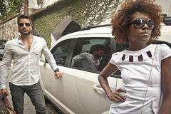 Couple arriving by limousine Stock Photos