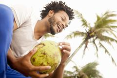 Low angle view of mid adult man drinking coconut milk, Ipanema beach, Rio De Stock Photos