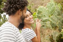 Couple pointing to names on cacti leaf, Ipanema beach, Rio De Janeiro, Brazil - stock photo