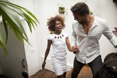 Couple arriving into apartment, holding hands - stock photo