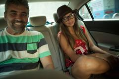 Portrait of mature man and young woman in back seat of taxicab, Rio De Janeiro, - stock photo