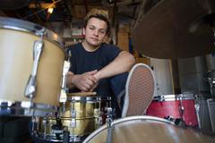 Portrait of young male drummer in basement Stock Photos
