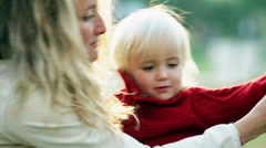 Mother is wearing his child with a sweater - stock footage