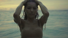 Sexy girl walking in the sea with wet hair at the sunset in slow motion. - stock footage
