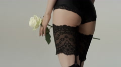 Unrecognizable sexy woman wearing lingerie posing with white rose in studio. - stock footage