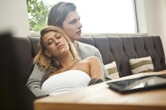 Young couple relaxing in hotel lobby - stock photo