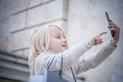 Young girl on stairway using touchscreen on smartphone, Cagliari, Sardinia, - stock photo