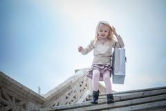 Young girl running down stairway carrying shopping bag, Cagliari, Sardinia, - stock photo