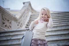 Portrait of young girl on stairway carrying shopping bag, Cagliari, Sardinia, - stock photo