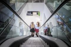 Two female friends moving up escalator in shopping mall Stock Photos