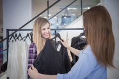 Two female friends shopping for sweater in boutique Stock Photos