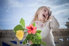 Young girl with flowers laughing and chatting on smartphone, Cagliari, Sardinia, - stock photo
