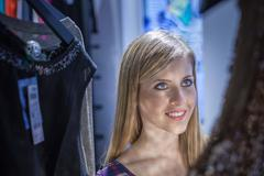 Young woman admiring dress in boutique - stock photo