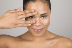 Portrait of young woman touching face with hand, dots of beauty cream on cheek Stock Photos