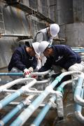Workers checking pipework on container ship at shipyard, GoSeong-gun, South - stock photo