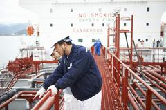 Two workers having discussion at shipping port, GoSeong-gun, South Korea - stock photo