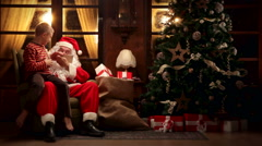 Child wearing striped pajamas gets a gift from Santa Claus - stock footage