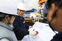 Workers looking at plans at shipyard, GoSeong-gun, South Korea Stock Photos