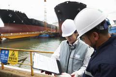 Workers having discussion at shipping port, GoSeong-gun, South Korea - stock photo