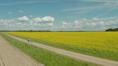 The girl and the guy go near the beautiful rape field Stock Footage