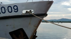 Unidentifiable white ship tied down to the dock Stock Footage