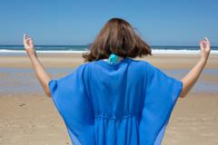 Beautiful positive brunette girl clothing in blue standing at the seaside on  Stock Photos